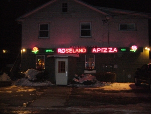 The neon-lit exterior of Roseland Apizza, covered with January snow.